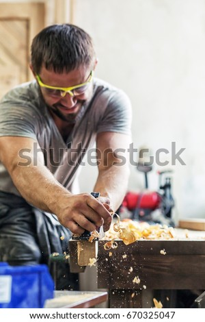 A young man with dark hair and wearing goggles is holding a black jack plane in his hands and is processing a wooden board in his hand flying wood sawdust in the workshop