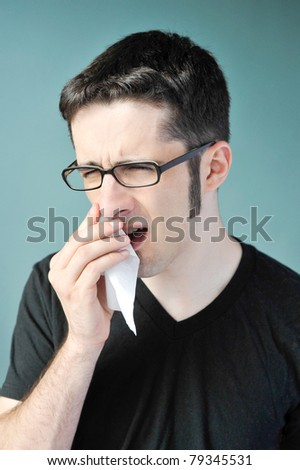 A young man with glasses and a nose bleed. - stock photo