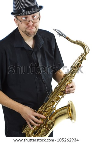 A young man with glasses wearing a hat and black shirt and holding a saxophone in his hands, making funny grimace - isolated on white - stock photo