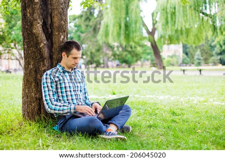 A young man with laptop outdoor