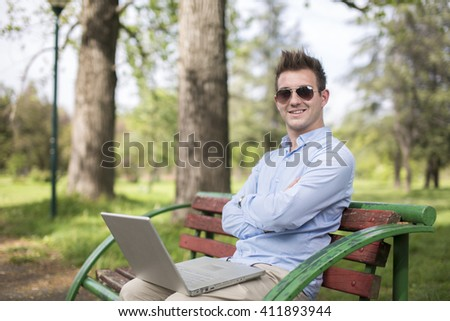 A young man with laptop outdoor - stock photo