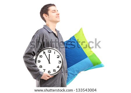 A young man with pillow and clock sleepwalking isolated on white background - stock photo
