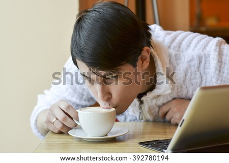 A young man, working at the computer and eating