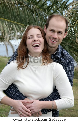 A young married couple have fun in a park. - stock photo
