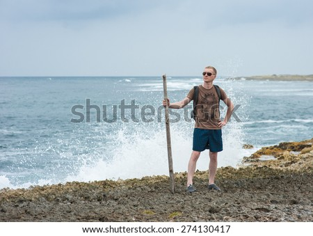 A young masculine guy is walking on the beach