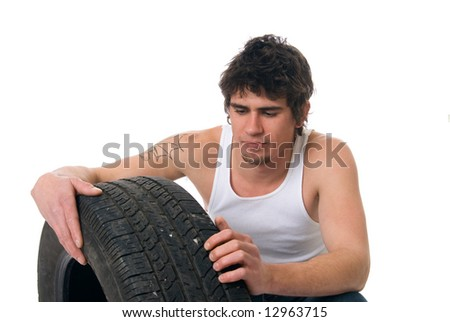 A young mechanic inspects a tire