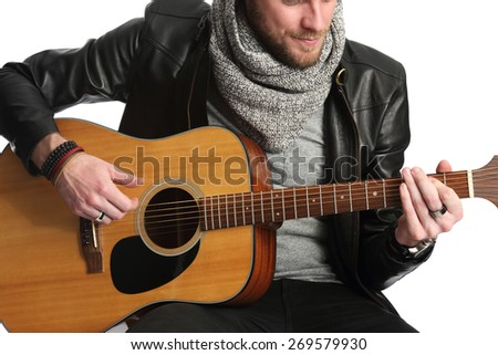 A young modern and attractive man wearing a black leather jacket and grey shirt sitting down playing on an acoustic guitar. White background.