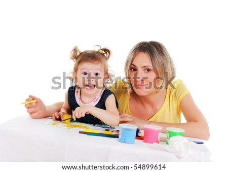 a young mom and her little daughter paint colors in this album - stock photo