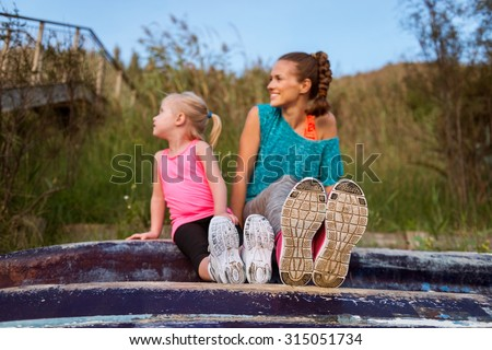 A young mother and daughter are sitting on an upturned boat. In the foreground, their running shoes. - stock photo