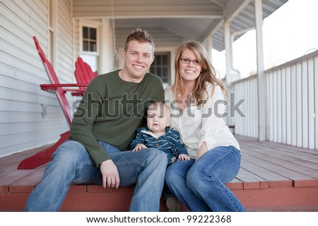 A young mother and father with their young son sitting on their back porch. - stock photo