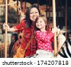 a young mother and her daughter riding on a merry go round at th - stock photo