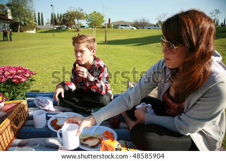 a young mother and son enjoy a picnic together in a park
