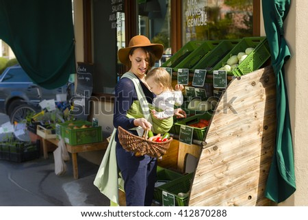 A young mother carrying her little baby in a sling before belly and buys vegetables at a market stall of a Health Food Shop.  Milk, cheese, eggs, sausage, vegetables in german language - stock photo