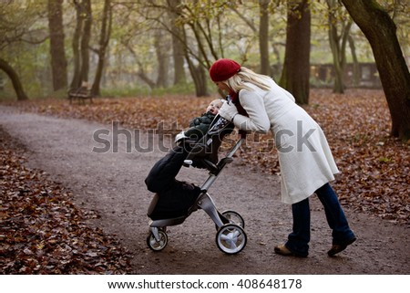 A young mother checking on her son in a stroller - stock photo