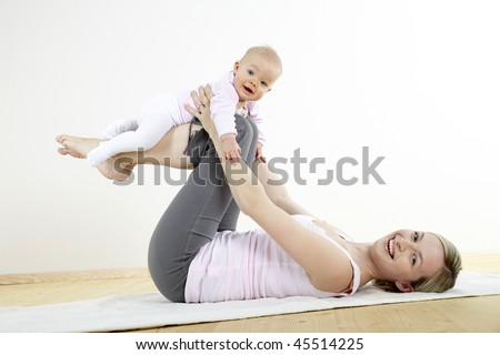 a young mother does physical fitness exercises together with her baby