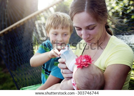 A young mother feeding milk the infant baby outdoors - stock photo