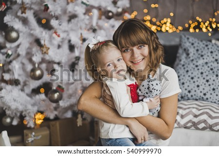 A young mother gently hugs the little girl before Christmas.