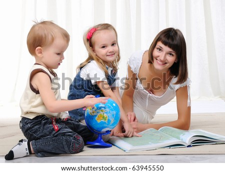 A young mother, her daughter and young son studying geography. Atlas and the globe. - stock photo