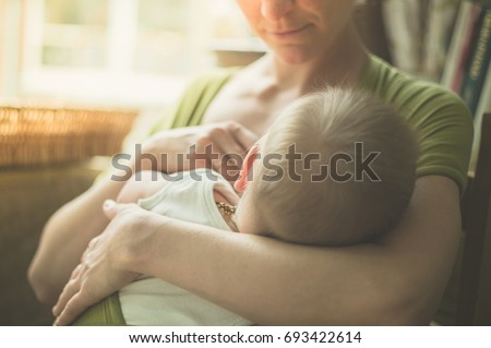 A young mother is breastfeeding her baby in a cafe by the window on a sunny day