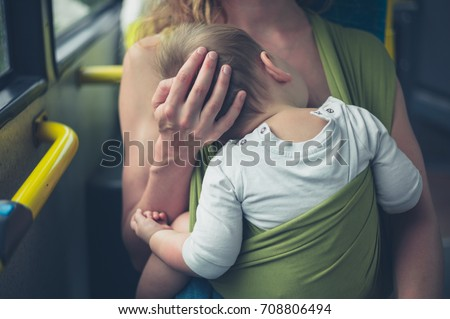 A young mother is breastfeeding her baby on  a bus