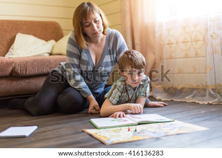 A young mother is engaged in training young son.