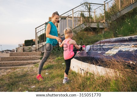 A young mother is holding her daughter's hand as they stretch their legs before they go for a run along the beach. The little girl is seen from behind. Mother and daughter are wearing fitness gear. - stock photo