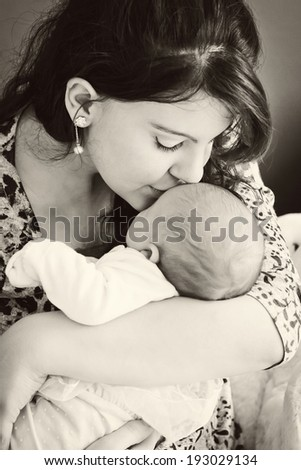 A young mother kissing her newborn baby BW - stock photo