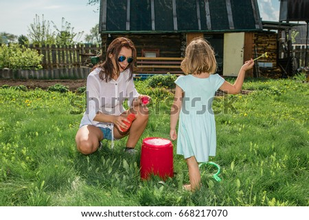 A young mother of European appearance and a girl 4-5 years old play in nature in soap bubbles. Both models wear sunglasses. Summer, sunny day.