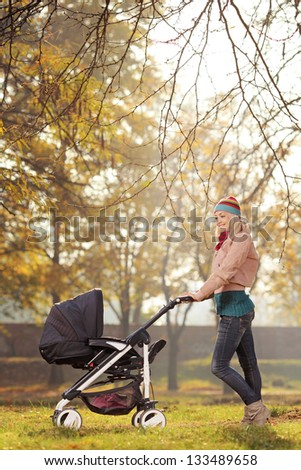 A young mother posing with a baby stroller in a park in autumn - stock photo