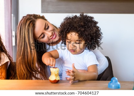 A young mother sitting at the kitchen table with her small afro child in her lap