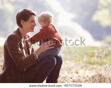 A young mother sitting on the grass holding her baby - stock photo