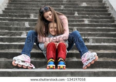 A young mother with her daughter sitting on the stairs in the Park with roller skates - stock photo
