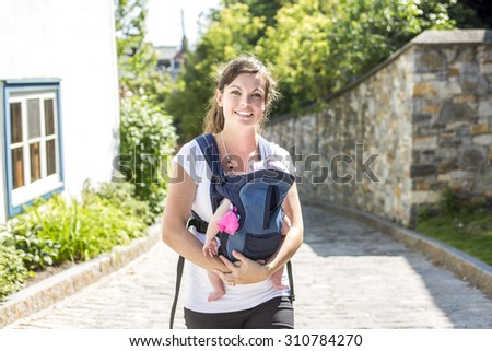 A Young mother with her toddler child in a baby carrier
