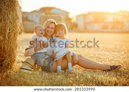 A young mother with two children - a little baby boy and a girl in a white dress sitting on a background of straw fields at sunset and smile - stock photo