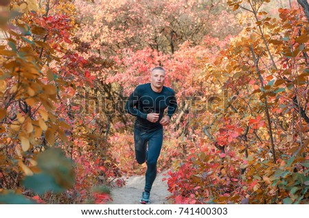 A young muscular athlete in a black sports leggins and shirt  runs through a beautiful red autumn forest. Photo show  active healthy lifestyle.