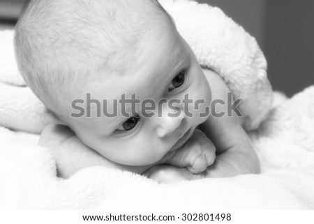 A young new born at age one month rests with her blanket in pure innocence. - stock photo