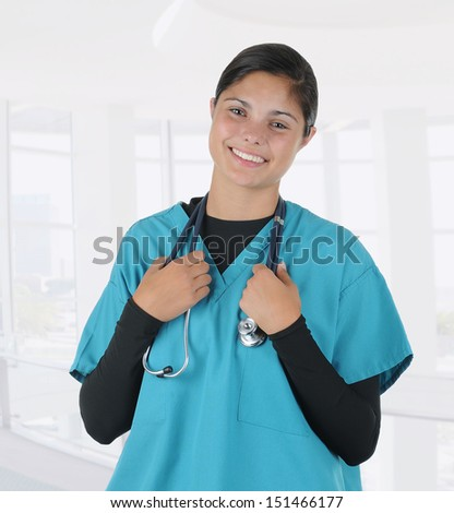 A young nurse or medical student holding a stethoscope that is draped around her neck. The woman is standing in a modern medical facility.