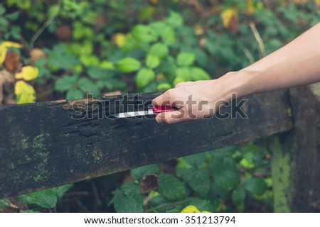 A young person is carving marks in a bench with a pocket knife - stock photo