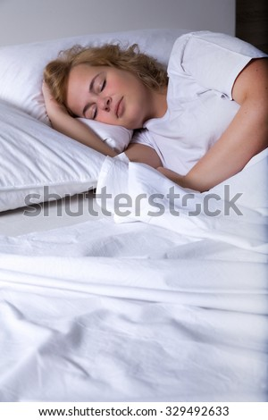 A young plus size woman sleeping in bed at night.