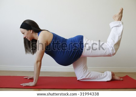 A young pregnant woman doing a buttock and leg muscle exercise on a mat. - stock photo