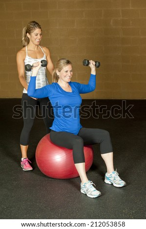 A young pregnant woman working out with an atletic female trainer at the gym. - stock photo