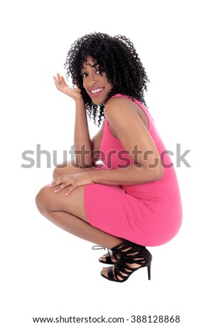 A young pretty African American woman in a pink dress and curly blackhair crouching on the floor, isolated for white background. - stock photo