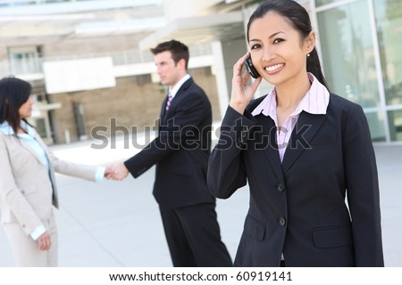 A young pretty asian woman on the phone at office building with team in background - stock photo