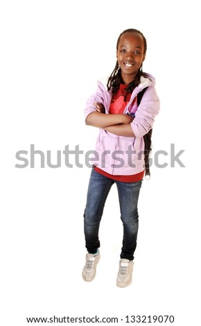 A young pretty black girl in jeans and a pink jacket standing for white background in the studio.