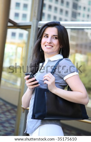 A young pretty business woman at office building - stock photo