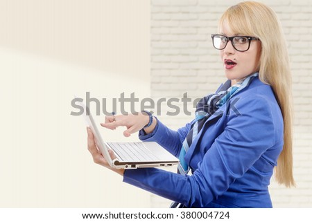 a young pretty business woman in blue suit with notebook in the office