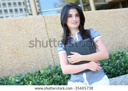 A young pretty business woman outside office building - stock photo