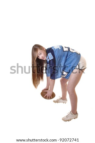 A young pretty girl in a football outfit and a football standing in the studio demonstrating how to play, with long brunette hair for white background. - stock photo