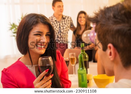 A young pretty girl with a glass of wine in hand, with a smile looking at the guy in front of her, while in the background see another young couple in the ambient house parties.