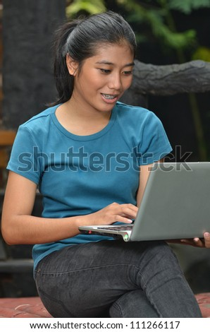 A young pretty southeast asian girls using a laptop at outdoor scene